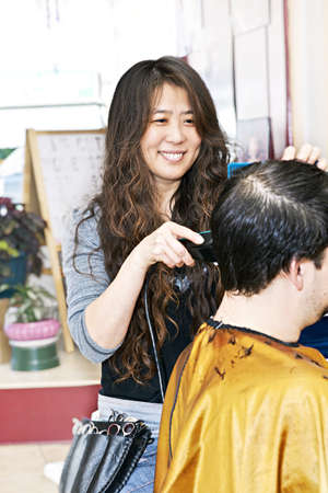 Happy hairdresser cutting hair in her salon Stock Photo - 8338232