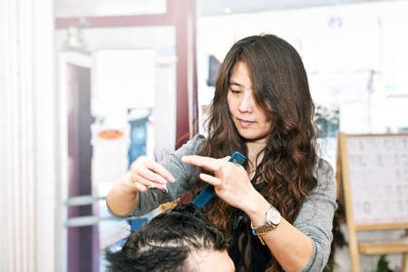 haircutter: Happy hairdresser cutting hair in her salon Stock Photo