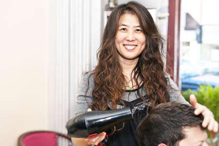 barber: Smiling hairstylist drying hair with hairdryer in her salon Stock Photo