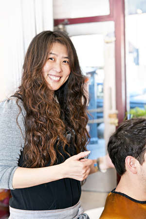 Smiling hairdresser cutting hair in her salon photo