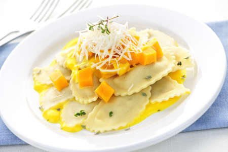 served: Gourmet squash ravioli dinner served with cheese on plate Stock Photo