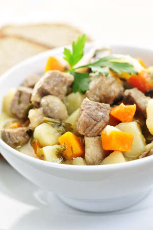 beef stew: Bowl of hearty beef stew with vegetables served with rye bread Stock Photo
