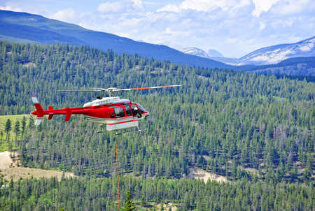 Red rescue helicopter flying emergency mission in mountains, Alberta Canada photo