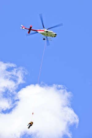 Hubschrauber, die Rettung Person durch Schleudergussverfahren baumelnd auf Seil zu retten