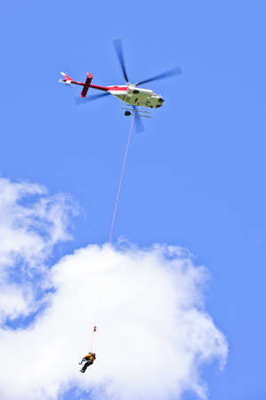 Rescue helicopter rescuing person by airlifting dangling on rope