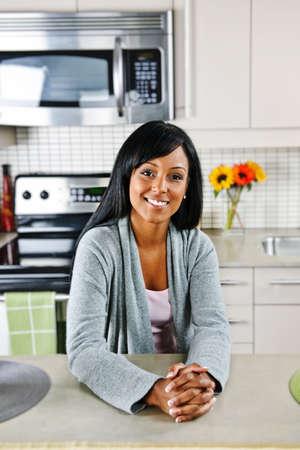 Smiling black woman in modern kitchen interior Stock Photo - 8380892