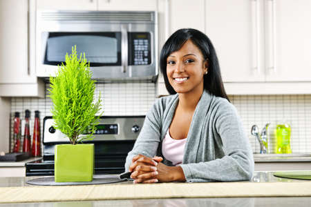 Smiling black woman in modern kitchen interior Stock Photo - 8380861