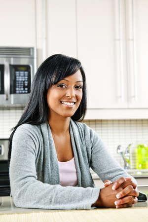 Smiling black woman in modern kitchen inter Stock Photo - 8380887