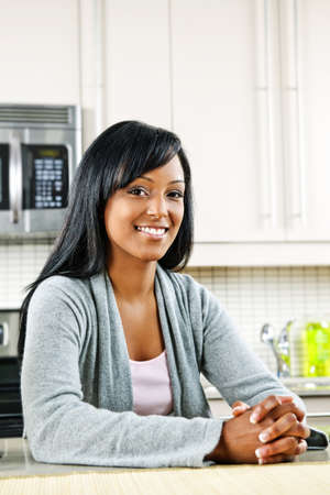 Smiling black woman in modern kitchen interior Stock Photo - 8380887
