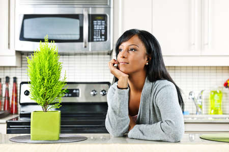 Thoughtful black woman in modern kitchen interior Foto de archivo