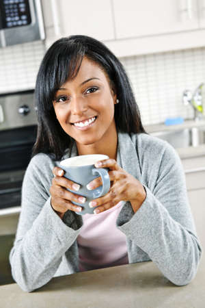 Smiling black woman holding coffee cup in modern kitchen interior photo