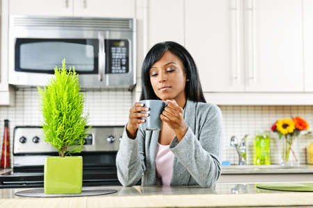 luxuries: Thoughtful black woman holding coffee mug in modern kitchen interior