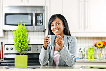 Smiling black woman holding coffee mug in modern kitchen interior Stock Photo - 8380865