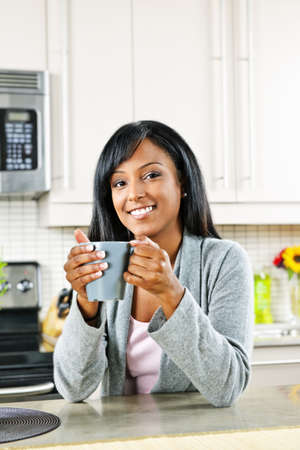 luxuries: Smiling black woman holding coffee cup in modern kitchen interior