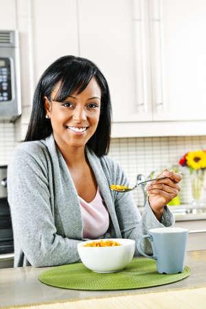 Smiling black woman having breakfast in modern kitchen interior Stock Photo - 8380840