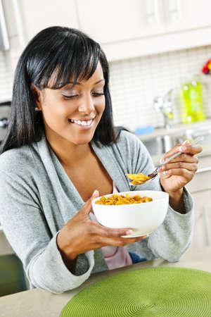 Smiling black woman having breakfast in modern kitchen interior Stock Photo - 8380891