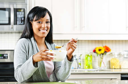 Smiling black woman having breakfast in modern kitchen interior photo