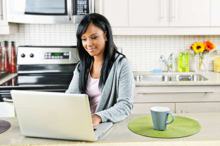 Smiling black woman using computer in modern kitchen interior Stock Photo - 8380805