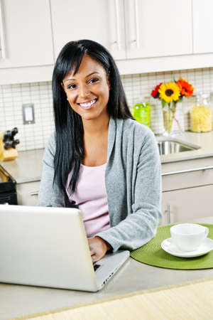 Smiling black woman using computer in modern kitchen interior Stock Photo - 8380791