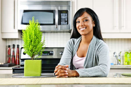 Smiling black woman in modern kitchen inter Stock Photo - 8436728
