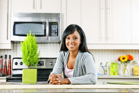 Smiling black woman in modern kitchen inter Stock Photo - 8436738