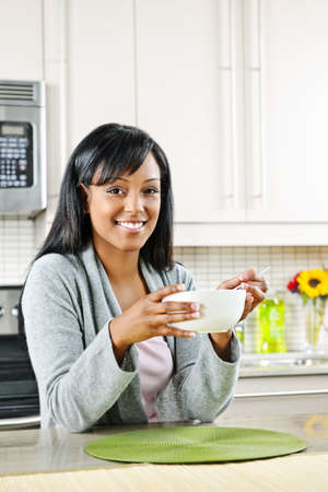 Smiling black woman having breakfast in modern kitchen interior Stock Photo - 8436727
