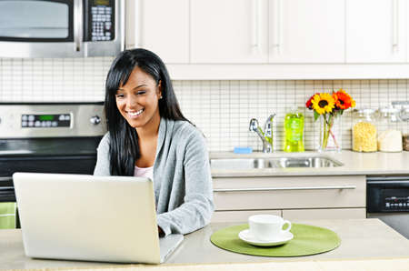 Smiling black woman using computer in modern kitchen interior 免版税图像