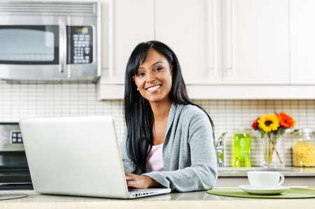 usando computadora: Sonriente mujer negra que utiliza el equipo en el interior de la cocina moderna