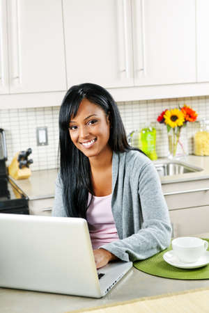 Smiling black woman using computer in modern kitchen interior Imagens