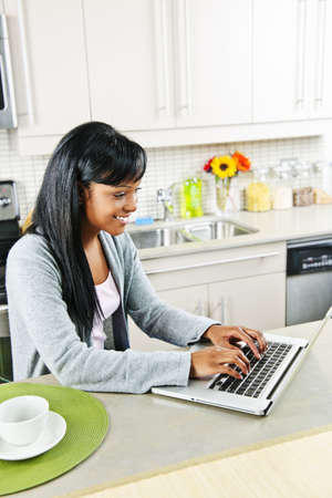 Smiling black woman using computer in modern kitchen inter Stock Photo - 8436739