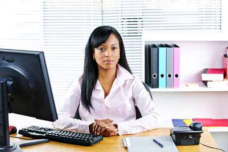 Portrait of young black business woman at desk in office Stock Photo - 8436685