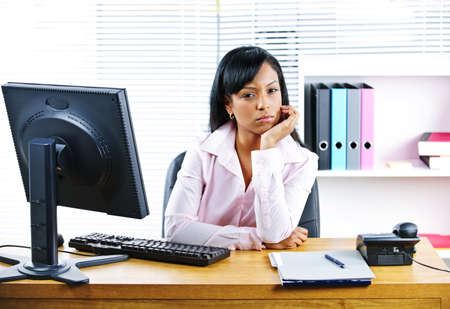 Portrait of young black unhappy business woman at desk in office photo