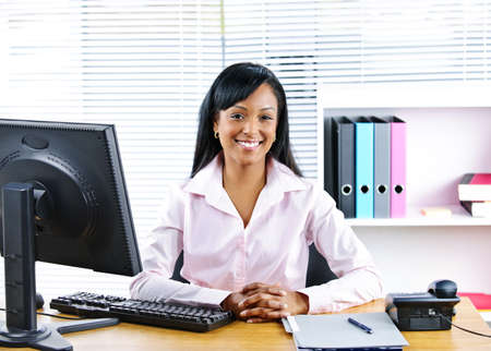 Portrait of smiling young black business woman at desk in office Stock Photo - 8436662
