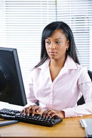 mecanograf�a: Retrato de mujer de serio de j�venes negros en escritorio escribiendo en equipo