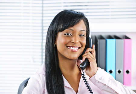 welcoming: Portrait of smiling black business woman on phone in office Stock Photo