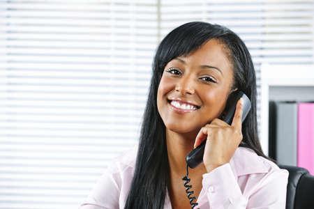 recepcionista: Mujer de negocios de retrato de sonriente negro sobre el tel�fono en la Oficina Foto de archivo