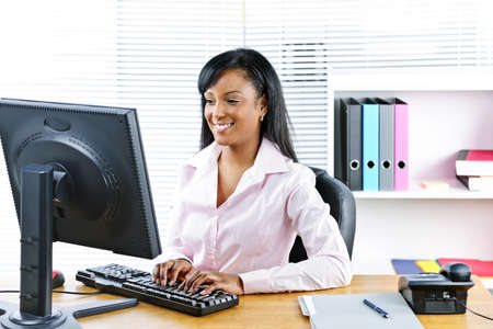 Portrait of happy black business woman at desk typing on computer Stock Photo - 8436684