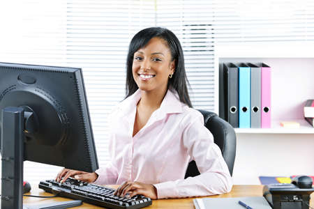 Portrait of happy black business woman at desk typing on computer photo