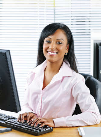 working on computer: Portrait of young smiling black business woman at desk typing on computer Stock Photo
