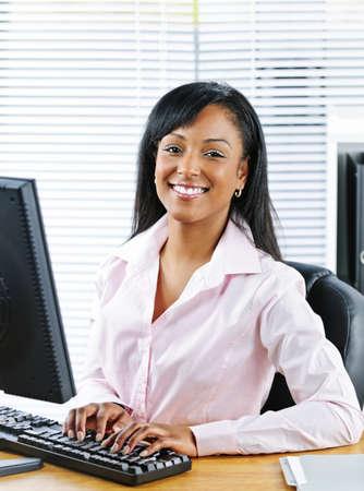 Portret van jonge glimlachend zwarte zaken vrouw op bureau te typen op de computer