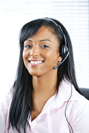 answering: Smiling black customer service and support woman wearing headset Stock Photo