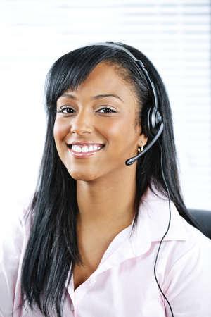 answering phone: Sonrisa de mujer de servicio y soporte de cliente negro, llevando el auricular
