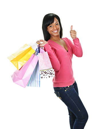 happy shopper: Young smiling black woman with shopping bags giving thumbs up