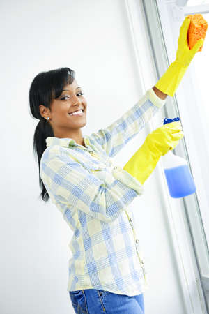 Smiling black woman cleaning windows with glass cleaner