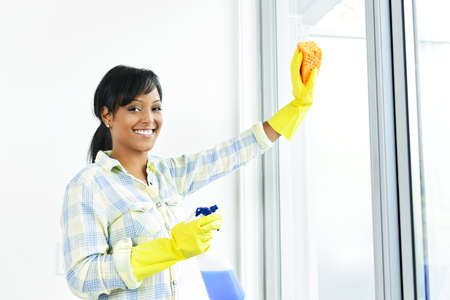 woman cleaning: Smiling black woman cleaning windows with glass cleaner