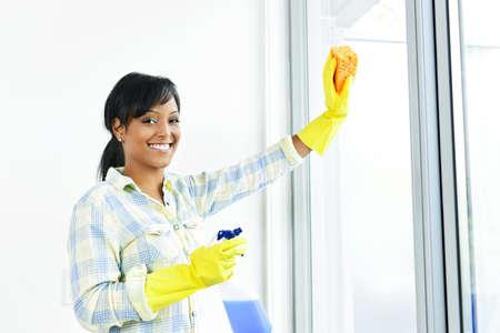 d�sinfectant: Souriant femme noire nettoyage windows avec verre plus propre