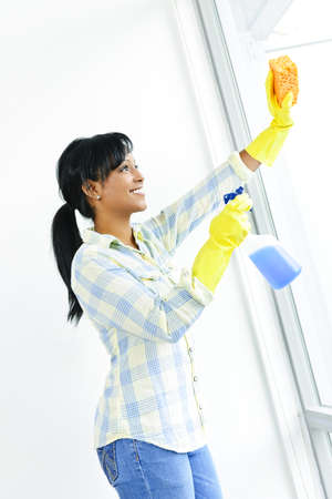 windows: Smiling black woman cleaning windows with glass cleaner