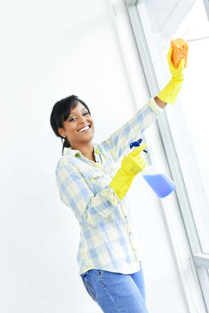 Smiling black woman cleaning windows with glass cleaner Stock Photo - 8871777
