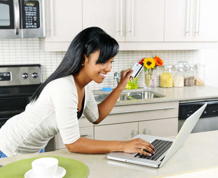 Smiling black woman online shopping using computer and credit card in kitchen photo