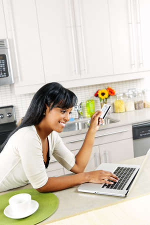 buying online: Smiling black woman online shopping using computer and credit card in kitchen